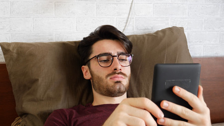 Young handsome man lying in bed and reading an ebook in his bedroom at home at night