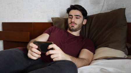 Young handsome man watching movie on cellphone lying in bed at home