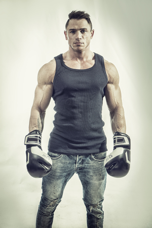 Handsome confident muscular man in boxing gloves looking at camera.