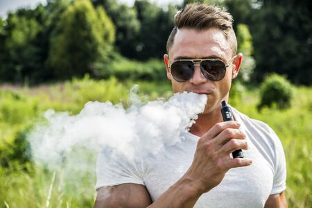 Handsome man standing in nature and vaping with electronic cigarette. Stock fotó