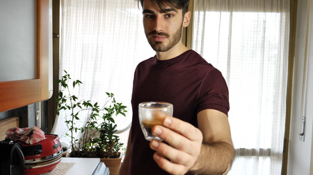 Young handsome man giving shot glass with liquor and looking at camera.