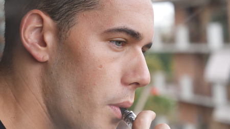 Handsome man standing on balcony and vaping with electronic cigarette. Stock fotó