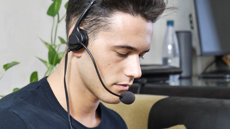 Young male home worker talking with customer or client through headset and microphone, working from his living room in front of computer Stock fotó