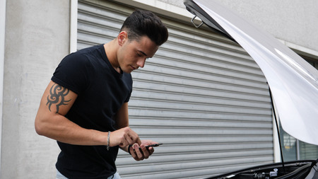 Young man trying to repair a car engine and seeking help with cell phone calling a mechanic Stock fotó