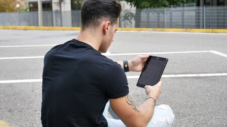 Young attractive man using tablet PC outdoor in city setting, in summer day Stock fotó