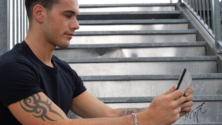 Young attractive man using tablet PC, watching a video, outdoor in city setting, in summer day Stock fotó