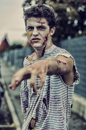 One teenage male zombie standing in empty city street in the evening, looking at camera. Halloween theme