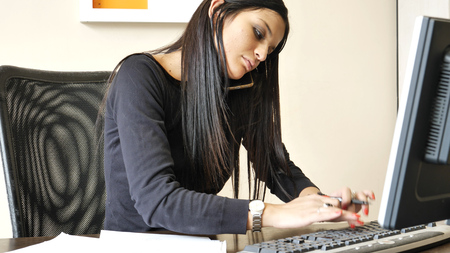 Serious attractive young businesswoman sitting at desk in office busy talking on phone