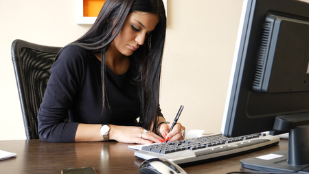Female office worker writing and signing check or cheque, while sitting at her desk and looking at computer screen