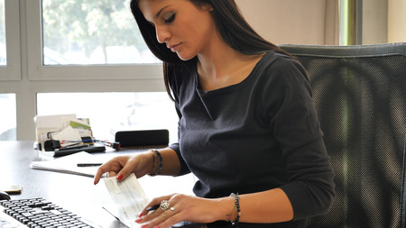 chequera: Oficinista de sexo femenino que escribe y que firma el cheque o el control, mientras que se sienta en su escritorio y está mirando la pantalla de ordenador