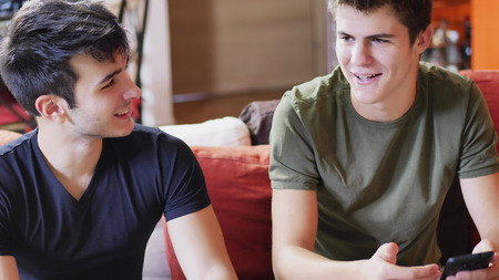Two young male friends talking and chatting while sitting on sofa at home, relaxing and having fun together.