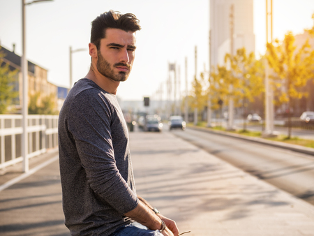 Attractive young bearded man portrait in urban environment, in a street, looking at camera