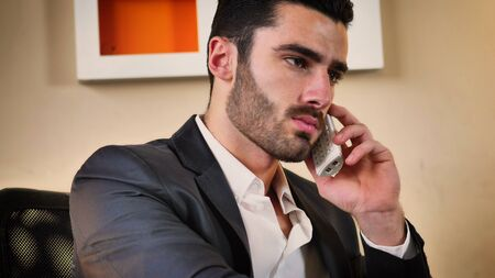 Successful handsome young businessman sitting at his desk in the office talking on phone