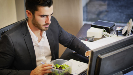 Elegant man in suit having lunch at table in office while talking on phone and watching computer.