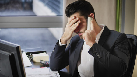 Serious attractive young businessman sitting at desk in office busy talking on phone and receiving upsetting news, getting worried and unhappy