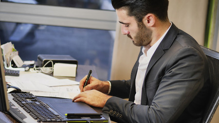 Successful handsome young businessman sitting at his desk in the office and looking at the computer screen while writing on sheet of paper
