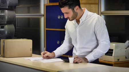 Handsome young businessman in white shirt standing at counter in office, receiving cup of coffee from colleague while working on documents