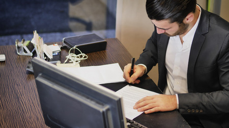 Successful handsome young businessman sitting at his desk in the office and signing document on sheet of paper
