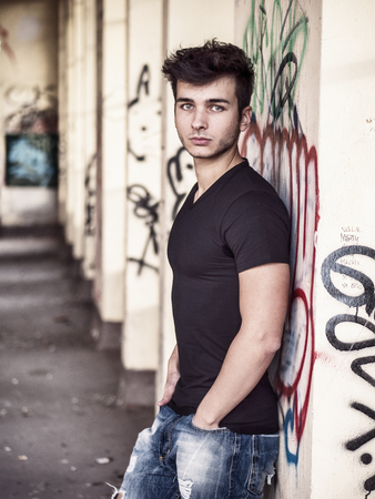 Friendly attractive young man looking at camera, large copy-space next to him, in urban environment