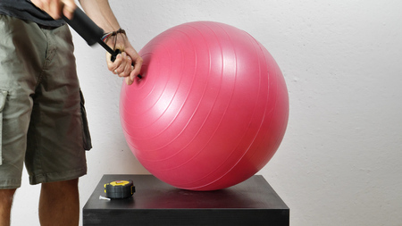 Crop shot of man pumping red fitness ball with small air pump.