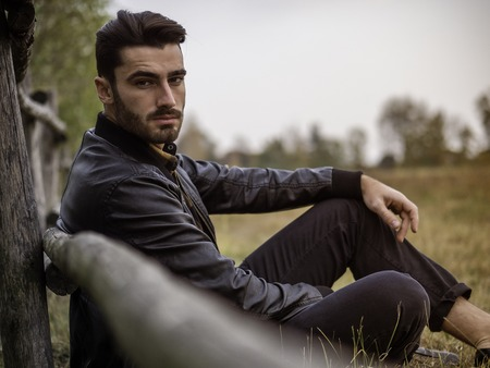 Portrait of sexy young man looking at camera while leaning on wooden fence in countryside