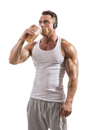 Muscular male bodybuilder holding protein shake bottle, wearing headphones. Isolated on white background in studio shot