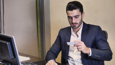 Handsome businessman sitting at table in his office and taking visiting or business card