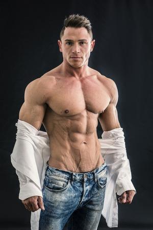 Male bodybuilder opening his shirt revealing muscular torso, on black background Standard-Bild
