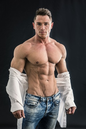 Male bodybuilder opening his shirt revealing muscular torso, on black background Фото со стока
