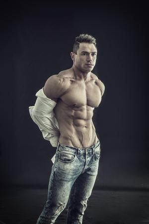 Male bodybuilder opening his shirt revealing muscular torso, on black background 写真素材