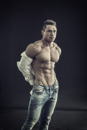 Male bodybuilder opening his shirt revealing muscular torso, on black background