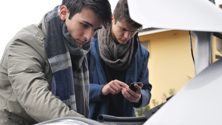 Young men looking up information while trying to repair car engine.