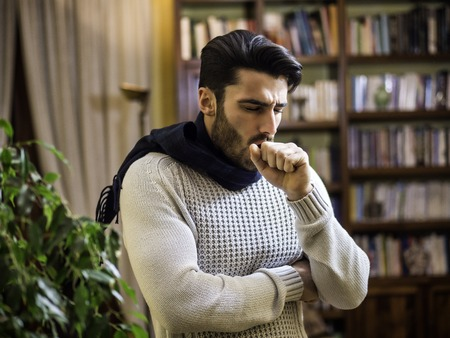Young man with scarf coughing and holding his neck because of cold and throat-ache, at home in his living room Stock fotó