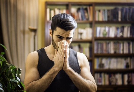 Young man blowing nose with handkerchief, indoor at home in his living room