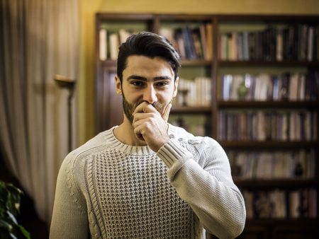 Handsome young man covering his mouth with hand, not laughing or in silence