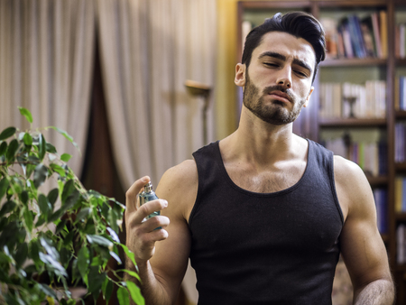 Handsome muscular young man in his home spraying cologne or perfume on neck