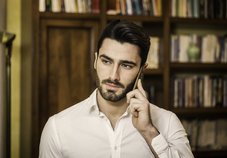 Handsome young man talking on telephone at home, looking to a side Stock fotó