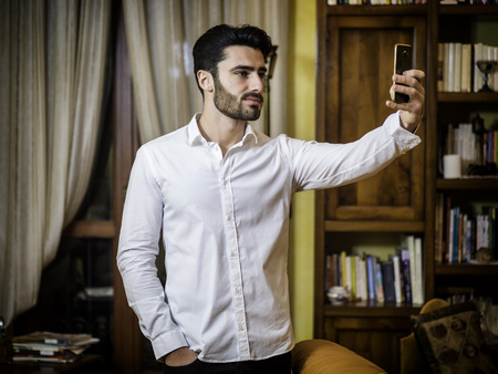 Handsome smiling young man doing selfie with smartphone at home in living room. Horizontal indoors shot Stock fotó