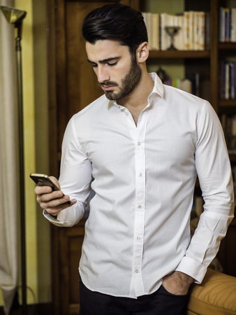 Attractive happy young man typing on cell phone, indoor shot in house living room
