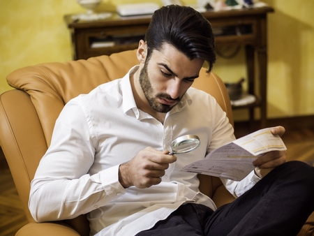 Young Man Sitting at Desk Scrutinizing Paper Contract with Magnifying Glass Prior to Signing