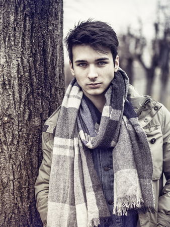 Handsome young man outdoor in winter fashion, wearing dark jacket and woolen scarf in city park looking at camera