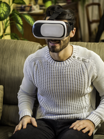 Young man using virtual reality viewer or headset at home, sitting on a couch