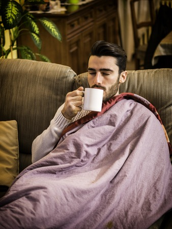 Young man sick with flu drinking herbal tea from a mug, resting under blanket on a couch