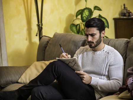 Young man sitting doing a crossword puzzle looking thoughtfully at a magazine, with his pencil to his mouth, as he tries to think of the answer to the clue