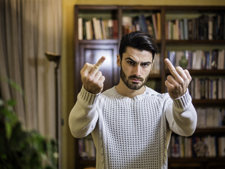 Handsome young man doing Screw You sign with middle finger, at home in his living room