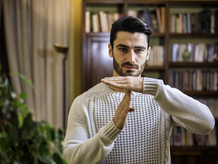 Attractive young man doing time-out sign, indoor shot inside a house