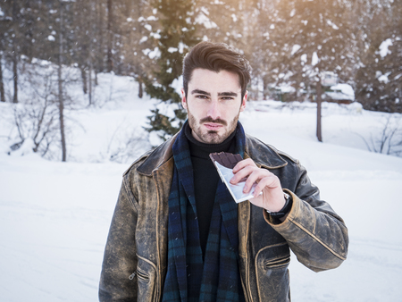 Portrait of young confident man biting chocolate bar on background of snows looking at camera.
