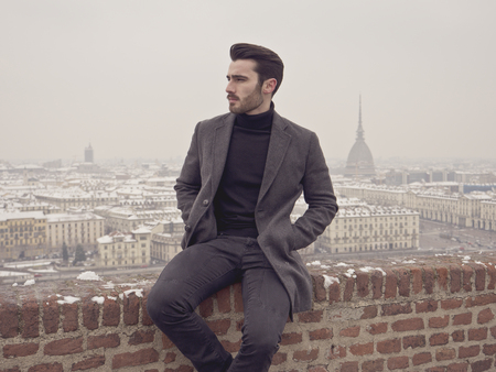 Handsome young man standing outside in winter, on balcony overlooking snowy cityscape or Turim, in Italy