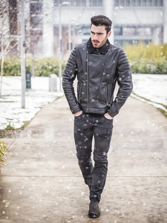Handsome young man standing outside in winter, in snowy Turim, in Italy