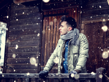 Young stylish man standing on porch of wooden rural house in snowy day. Stock fotó